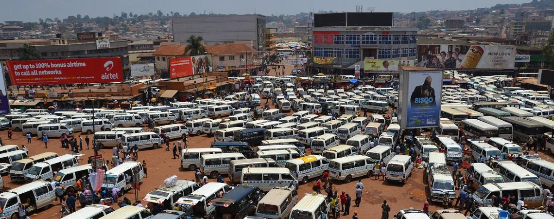 View from above of a lot filled with parked minibuses, billboards, vendors and other people.